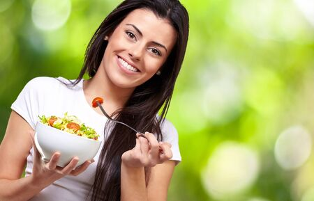 portrait of healthy woman eating salad against a nature background