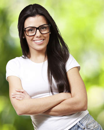 pretty young woman with glasses crossing her arms against a nature background photo