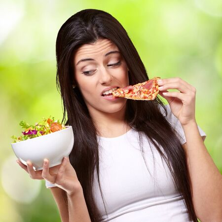 portrait of young woman eating pizza and looking salad against a nature background photo