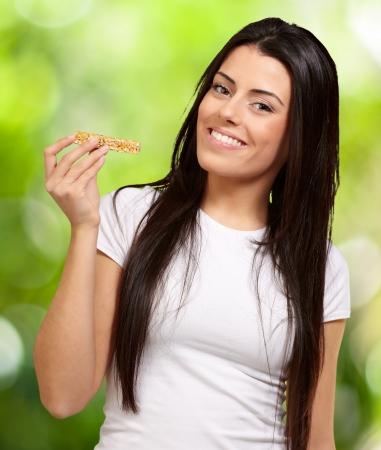 barra de cereal: Retrato de mujer joven comiendo barra de cereal contra un fondo de naturaleza Foto de archivo