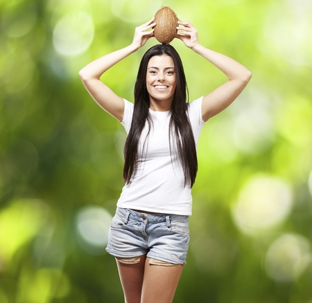 young girl holding a coconut on her head against a nature background photo
