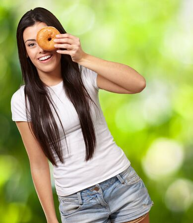portrait of young woman looking through a donut against a nature background Stock Photo - 14683295