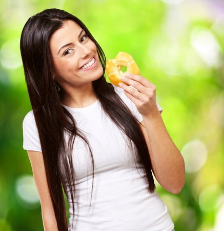 portrait of young woman eating a donut against a nature background photo