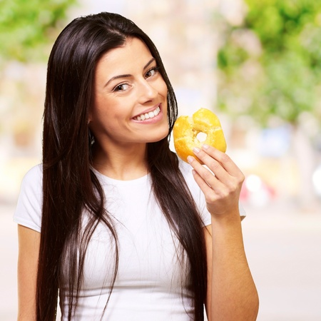portrait of young woman eating a donut against a plants background photo