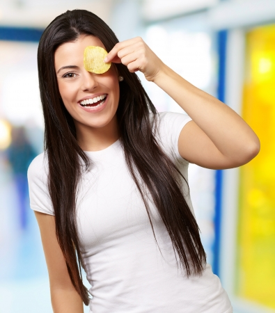 portrait of young woman holding a potato chip in front of her eye indoor photo