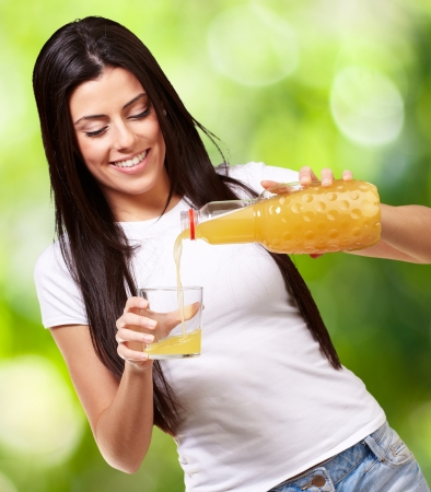 portrait of young woman pouring orange juice on glass against a nature background photo