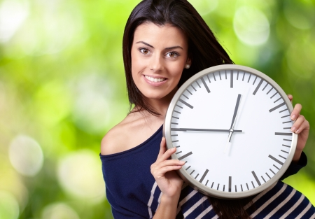 portrait of young woman holding clock against a nature background photo