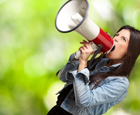 portrait of young woman screaming with megaphone at park photo