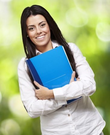 fresh graduate: young woman smiling and holding a notebook against a nature background