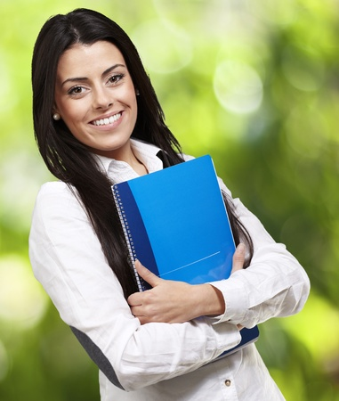 young woman smiling and holding a notebook against a nature background photo