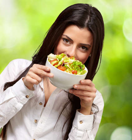 portrait of young woman holding a fresh salad against a nature background Stock Photo - 14706816