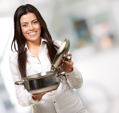 woman cooking: portrait of young girl opening sauce pan indoor Stock Photo