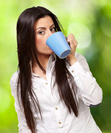 portrait of young woman drinking against a nature background Stock Photo - 14703983