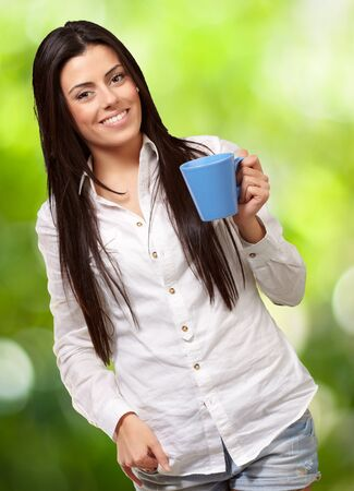 young girl holding cup against a nature background Stock Photo - 14704241
