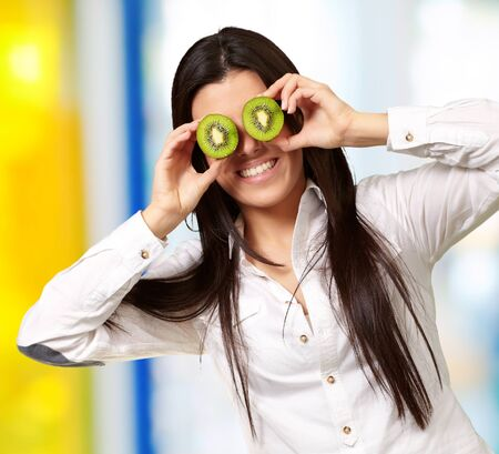 portrait of young girl holding kiwi slices in front of her eyes indoor Stock Photo - 14703939