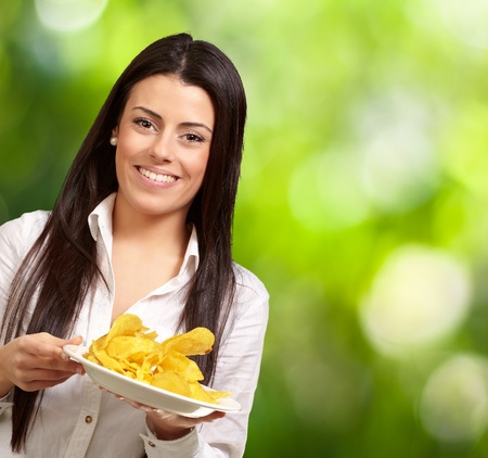 portrait of young woman holding a potato chips plate against a nature background