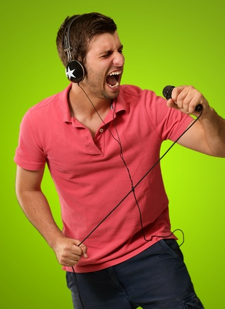 vocalist: Man holding microphone in hands Isolated on green background