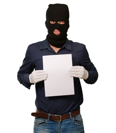 Man wearing a robber mask showing a blank paper on white background Stock Photo - 14760807