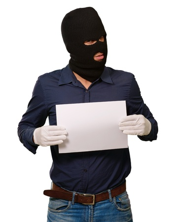 thievery: Man wearing a robber mask showing a blank paper on white background Stock Photo