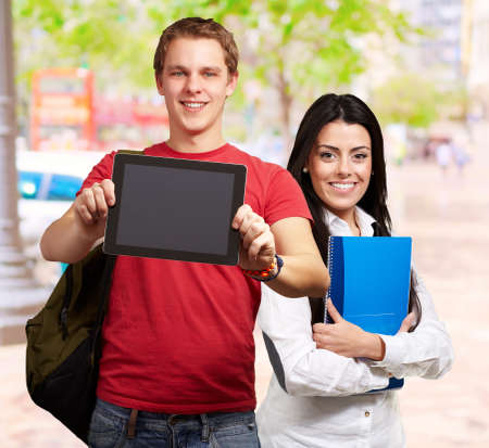 students holding tablet and books, outdoor photo