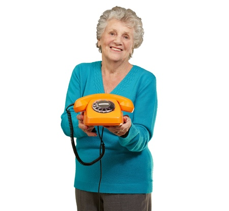 beautiful mature woman: portrait of a happy senior woman holding a vintage telephone Stock Photo