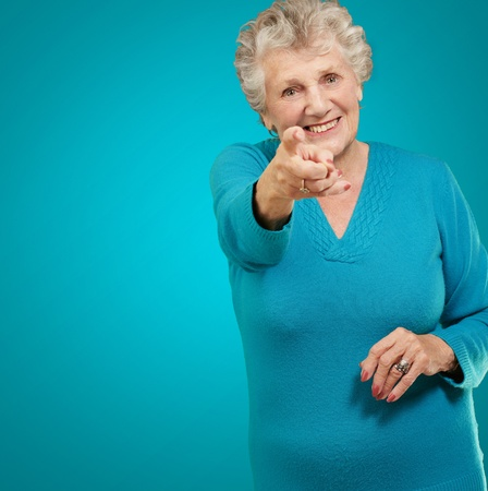 Portrait Of Woman Pointing Her Finger On Turquoise Background photo