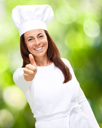 Chef woman showing thumbs up, outdoor photo