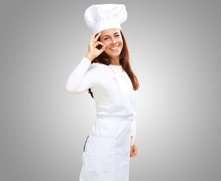 Woman chef gesturing on grey background photo