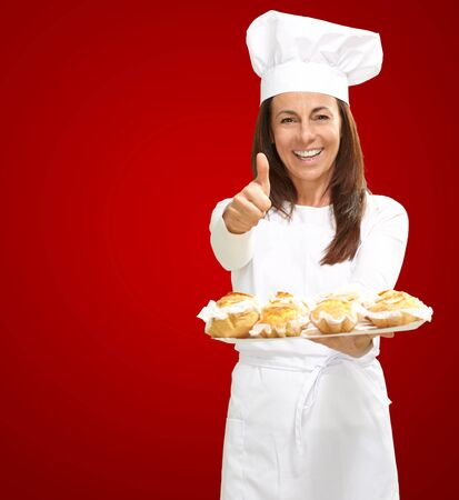 Woman chef holding baked food on red background photo