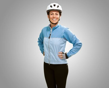 Women smiling with hands on hip isolated on gray background photo