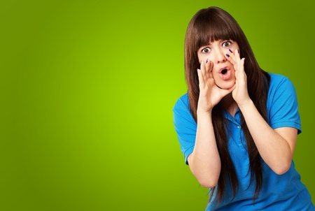 portrait of a teenager screaming on green background photo