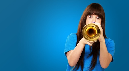 portrait of a teenager playing trumpet on blue background photo