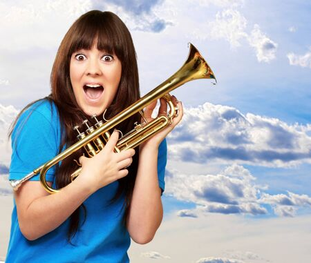 surprised woman holding trumpet, outdoor photo