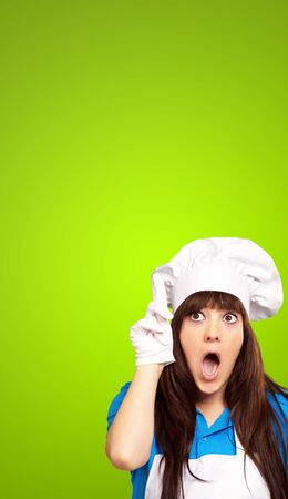 portrait of female chef shocked on green background photo