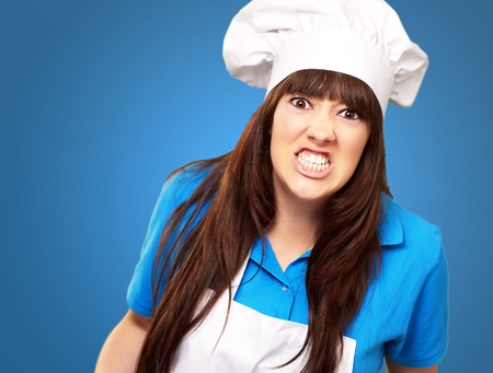 overwrought: portrait of a female chef clenching on blue background