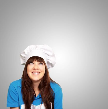 portrait of a female chef looking up on gray background photo