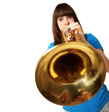 Retrato de una chica joven que sopla la trompeta en el fondo blanco