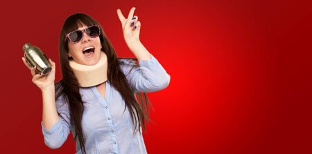 Woman Wearing Neckbrace Holding A Shaker Isolated On Red Background photo