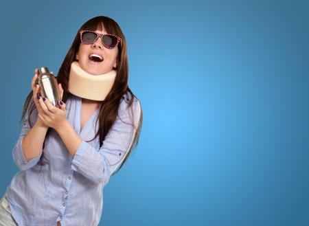 causation: Woman Wearing Neckbrace Holding A Shaker Isolated On Blue Background