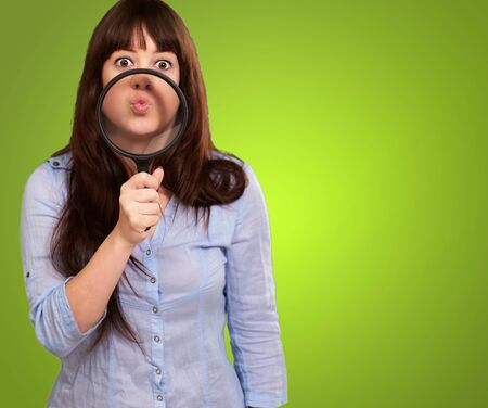causation: Woman Holding Magnifying Glass On Mouth Isolated On Green Background