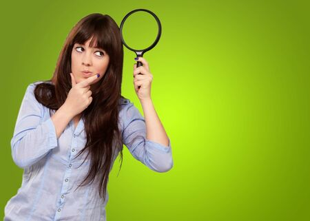 Portrait Of A Girl Holding A Magnifying Glass And Thinking On Green Background