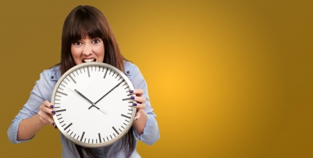 making a face: A Young Girl Holding A Clock And Angry On Yellow Background