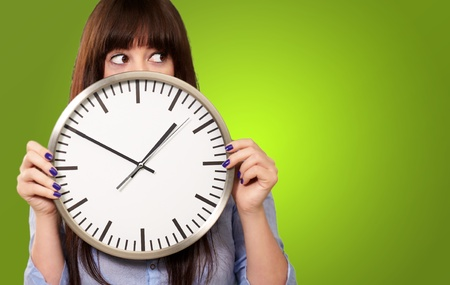 A Young Girl Holding A Clock On Green Background Stock Photo