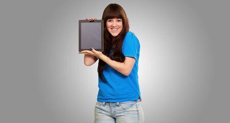 Woman Holding Ipad Isolated On Gray Background photo