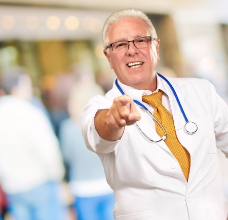 Portrait Of A Senior Doctor Pointing, outdoor photo
