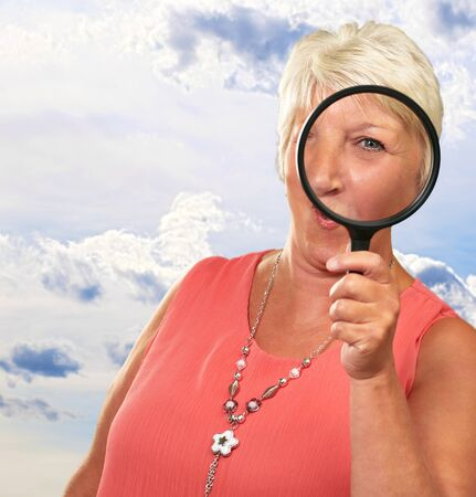 Senior Woman Looking Through A Magnifying Glass, Outdoor photo