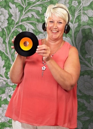 Portrait Of A Senior Woman Holding A Disk On Wallpaper photo