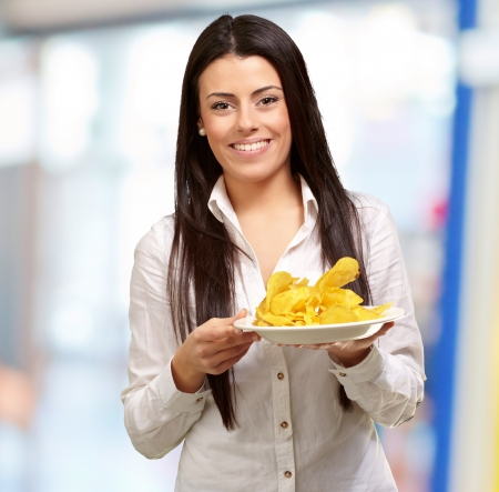 portrait of young woman holding a potato chips plate indoor photo