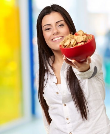 portrait of young woman offering cereals bowl indoor photo