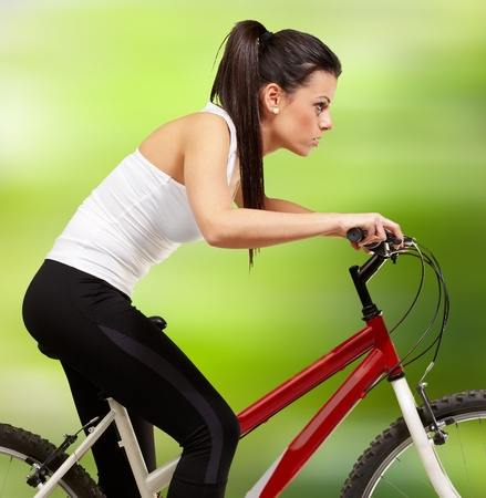 young sporty girl cycling against a nature background photo
